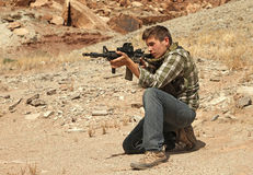 Teenage boy shooting rifle. Teenage boy shooting AR-15 submachine gun Royalty Free Stock Image