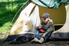 Teenage boy sits near a tent on a green meadow. At sunny morning listens to the music on the player and relaxes Stock Photo