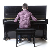 Teenage boy sits at upright piano in studio Royalty Free Stock Photo