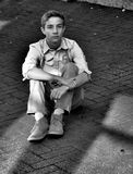 Teenage boy sitting in an alley. Teenage boy sitting on a brick street or sidewalk with a blank look on his face Royalty Free Stock Photo