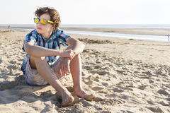 Teenage boy sitting on the beach Stock Images