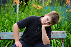 Teenage boy sitting on a bench Stock Image