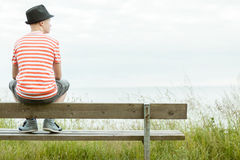 Teenage boy sitting on a bench above the sea Royalty Free Stock Photos
