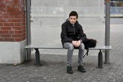Boy waiting at school bus stop. Teenage boy sitting on a bench at the bus stop waiting on his transport to school royalty free stock photos