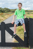Teenage boy sitting on black wooden fence in nature Royalty Free Stock Images