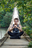 Teenage boy sitting on a bridge Royalty Free Stock Photography