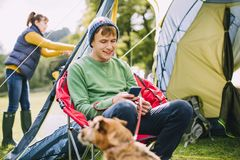 Teenager using Smart Phone on Camping Trip. Teenage boy is sitting in a camping chair by his tent, engrossed in his smart phone while his Mum puts up the tent royalty free stock photos