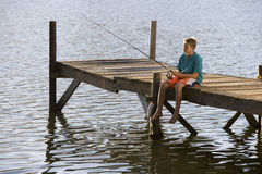 Teenage boy (13-15) sitting at edge of jetty, fishing in lake Stock Photos
