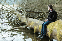 Teenage boy sitting on a fallen tree trunk Stock Photos