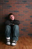 Teenage boy sitting on floor with arms on knees Royalty Free Stock Photo