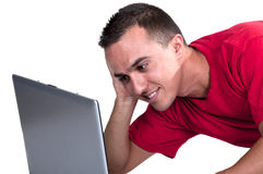 Teenage boy sitting on the floor with computer. On white background Royalty Free Stock Photography