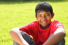 Teenage boy sitting on grass in bright sunshine Stock Images