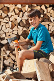 Teenage boy sitting on heap of firewood. Preparing to chop and stack it in a woodshed stock photos