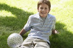Teenage Boy Sitting In Lawn With A Ball Royalty Free Stock Photo