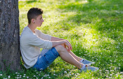 Teenage boy sitting on meadow full of white flowers in summer Royalty Free Stock Photos