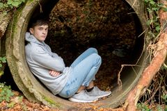 Teenage boy sitting in an old drainage pipe. On an autum day Stock Images