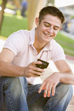 Teenage Boy Sitting Outdoors Using Mobile Phone. Smiling Royalty Free Stock Photo