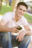 Teenage Boy Sitting Outdoors Using Mobile Phone. Smiling Royalty Free Stock Images