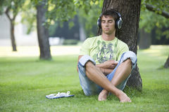 A teenage boy sitting in a park listening to music Royalty Free Stock Images