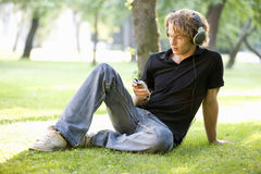 A teenage boy sitting in a park listening to music Royalty Free Stock Photos