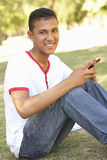Teenage Boy Sitting In Park Reading Text Message On Mobile Phone Royalty Free Stock Photos