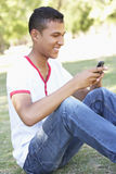 Teenage Boy Sitting In Park Using Mobile Phone Stock Photos