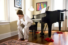 Teenage boy sitting on piano bench looking down Stock Photo