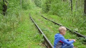 A lonely teenage Boy sitting on railroad tracks. A teenage boy is sitting on a railway track stock video footage