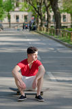 Teenage boy sitting on skateboard in the middle of street Stock Photography