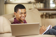 Teenage Boy Sitting On Sofa At Home Doing Homework Using Laptop Computer Royalty Free Stock Image