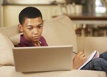 Teenage Boy Sitting On Sofa At Home Doing Homework Using Laptop Computer Stock Photo