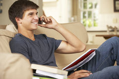 Teenage Boy Sitting On Sofa At Home Doing Homework Using Mobile Phone Stock Photography
