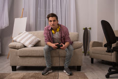Teenage boy sitting on sofa playing computer games. Stock Photos