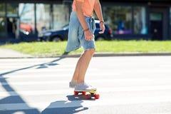Teenage boy on skateboard crossing city crosswalk Royalty Free Stock Photography