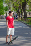 Teenage boy with skateboard standing in middle of street Royalty Free Stock Photography