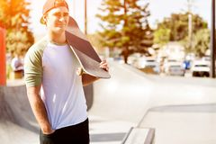 Teenage boy with skateboard standing outdoors Royalty Free Stock Photos