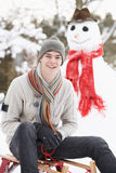 Teenage Boy With Sledge Next To Snowman Royalty Free Stock Photography