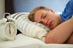 Teenage Boy Sleeping Through Alarm. In The Morning Stock Photos