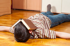 Teenage boy sleeping with book covering his face stock image