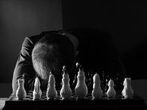 Teenage boy slumped over the chessboard. Teenage boy slumped over the  chessboard. Black and white photo Royalty Free Stock Images