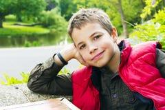 Teenage boy smiling against green background. Cute teenage boy smiling against green background Royalty Free Stock Image