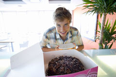 Teenage boy (16-18) smiling by chocolate cake in box, portrait Royalty Free Stock Photo
