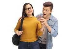 Teenage boy sneaking up on a female tudent to grab a bite of her. Teenage boy sneaking up on a female student to grab a bite of her chocolate isolated on white Royalty Free Stock Image