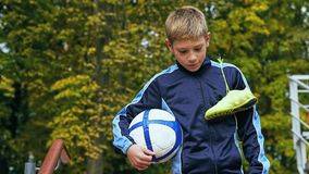 Smiling teenage boy with a soccer ball in his hand and soccer boots on the shoulder against the background of the. Teenage boy with a soccer ball in his handand stock image
