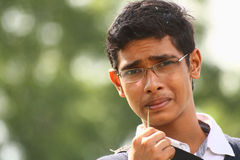 Teenage boy with specs biting grass blade. Teenage indian boy with specs biting a grass blade Royalty Free Stock Photo