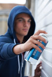 Teenage Boy Spray Painting Door Royalty Free Stock Image