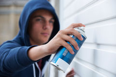 Teenage Boy Spray Painting Garage Door Stock Photography