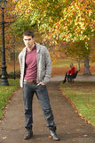 Teenage Boy Standing In Autumn Park With Female. Figure On Bench In Background Royalty Free Stock Images