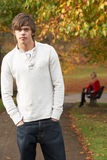 Teenage Boy Standing In Autumn Park With Female. Figure On Bench In Background Royalty Free Stock Image