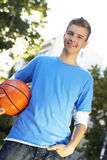 A teenage boy standing with a basketball. Stock Photos